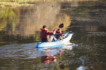 Father and son kayaking together on a lake, back view