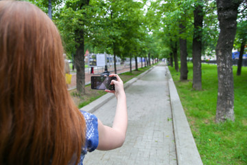 Young woman taking a photo with her phone in the park