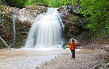 girl stands near the beautiful wide waterfall and looking