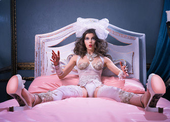 Girl as a doll, sitting on the bed in shoes