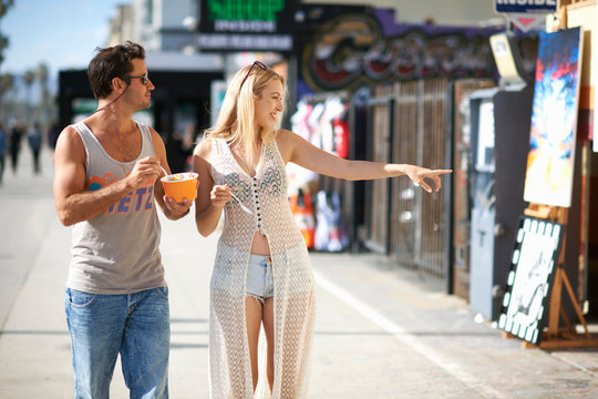Couple eating frozen yoghurt and pointing at shops on sidewalk, Venice Beach, California, USA