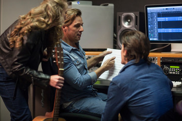Musicians talking with music producer in music studio