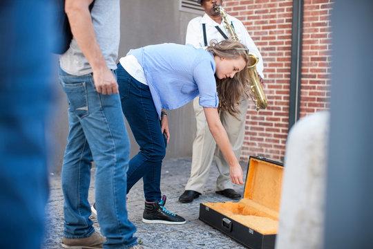 Pedestrian throwing money into street musician's music case