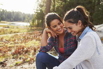 Happy lesbian couple laughing together in the countryside