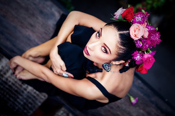 young attractive brunette in wreath of multicolored roses