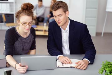 junge leute sitzen am schreibtisch und schauen gemeinsam auf laptop