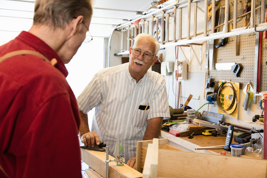 Senior men planing woodblock in carpentry workshop