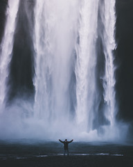 Standing strong - Person standing in front of gigantic waterfall.