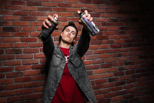 Graffiti man in cap getting ready to spray aerosol can