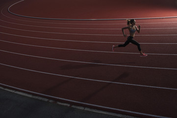 High angle view of young female athlete running on race track