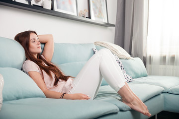 Happy young woman lying on couch and relaxing at home. Casual style indoor shoot