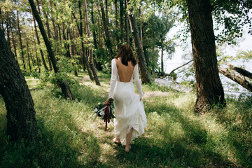 The bride in a white vintage dress walking in the woods