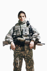 Portrait of female soldier standing with rifle against white background
