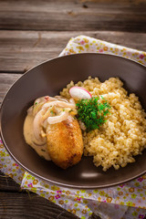 Fried meat with couscous garnish in bowl.