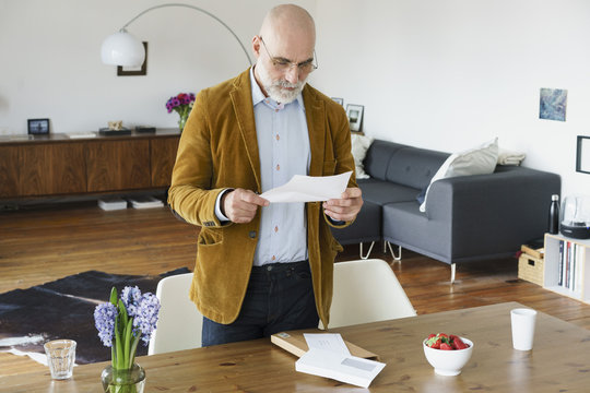 Mature man standing by table and reading letter at home