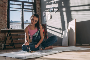 Woman painting while sitting on floor in art studio