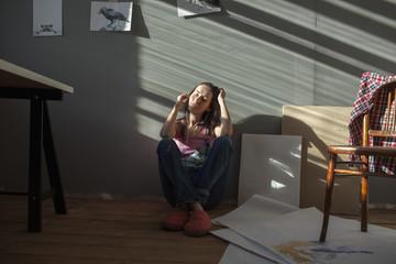 Female painter listening music while sitting at art studio