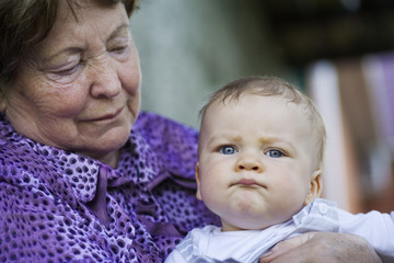 A senior woman holding a baby