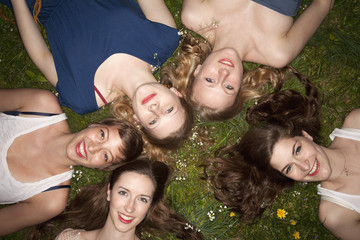 Five cheerful female friends lying in the grass, head and shoulders