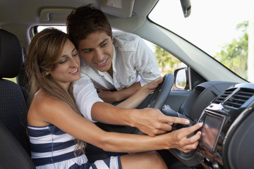 A man leaning in car window helping his girlfriend with the GPS