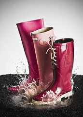 Three pink rubber boots splashing in a puddle