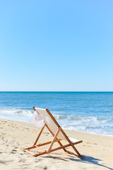 Back View Of Woman's Hat and Deckchair On Sandy Beach