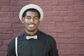 A cheerful young black man wearing bow tie, suspenders and hat