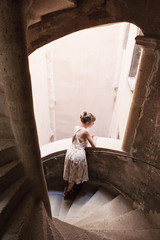 A woman leaning on a staircase railing and looking outside