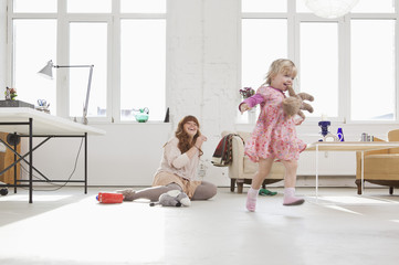 A young girl carrying a stuffed toy in her mouth running around