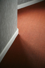 Contrasts of red carpet against white baseboard and gray wall