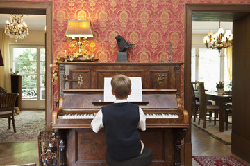 A boy practicing on an old-fashioned upright piano