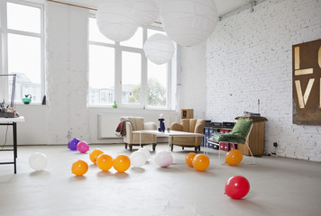 Multi colored balloons on the floor of a modern living room