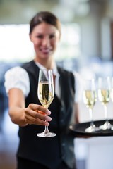 Portrait of smiling waitress offering a glass of champagne