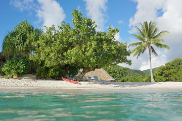 Tropical shore near a resort with a kayak and lounge chairs on the beach, seen from water surface, Fare, Huahine island, south Pacific, French Polynesia