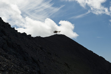 The Wetterstein, Tirol, Austria, Helicopter in distance above a silhouetted mountain