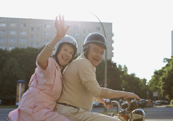 Senior couple happy on motorbike as woman waves