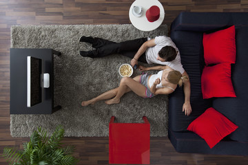 A couple eating popcorn and watching TV in their living room, overhead view
