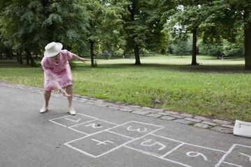 Senior woman rolls a stone as she plays hopscotch