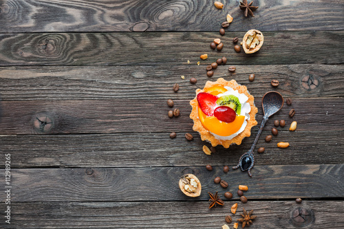 Wooden rustic background with fruit tart and spices - peanuts, anise ...