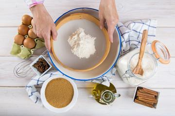 Chef de cocina tamizando harina para cocinar magdalenas y otros postres y dulces para el desayuno