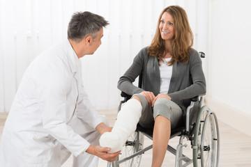 Physiotherapist Examining Leg Of Patient