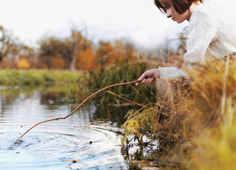 A woman poking at the water with a stick