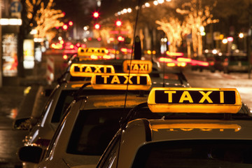 Detail of taxi cabs parked in a row at night Fototapete