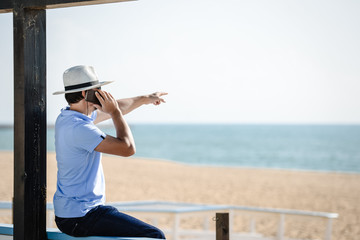 Tuinposter Male wear hat talking on phone and pointing at sea and blue sky.