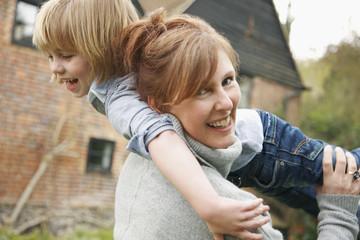 A mother holding her son over her shoulder