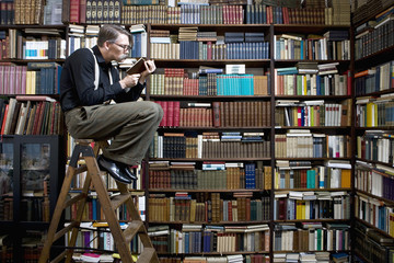 A man sitting on a ladder in a bookstore reading a book