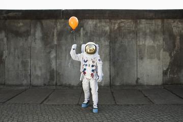An astronaut on a city sidewalk holding a balloon