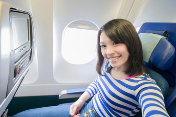 Happy woman sitting in airplane