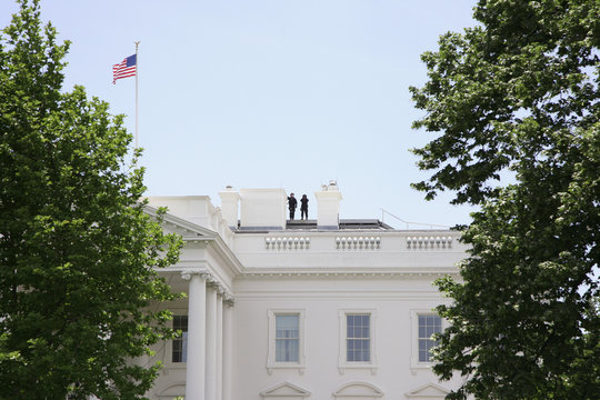 Two people standing on the roof of the Whitehouse, Washington DC, USA
