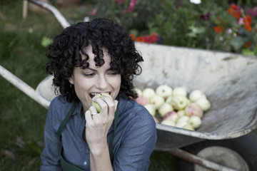 A woman taking a bite from a freshly picked apple